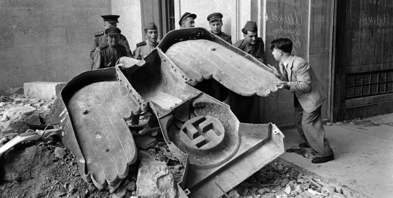 cms_1323/russian-soldiers-and-a-civilian-struggle-to-move-a-large-bronze-nazi-party-eagle-that-once-loomed-over-a-doorway-of-the-reich-chancellery-in-berlin-1945.jpg